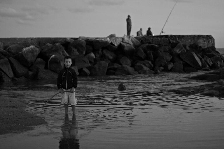 Niño en la playa con pescadores.